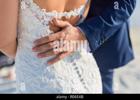 Perfect beach wedding, newlyweds couple, honeymooners. Sunset and love mood. The bride and groom under archway on beach. Romantic sunset, twilight - Stock Photo