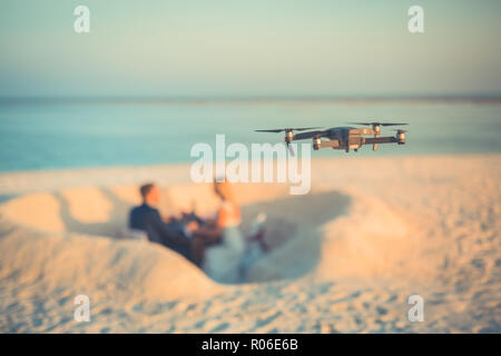 Perfect beach wedding, newlyweds couple, honeymooners. Sunset and love mood. Drone taking footage of married couple, digital technology concept - Stock Photo