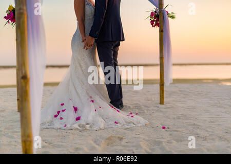 Perfect beach wedding, newlyweds couple, honeymooners. Sunset and love mood. The bride and groom under archway on beach. Romantic sunset, twilight - Stock Photo
