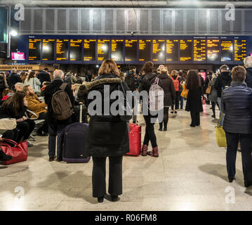 Passengers, men and women, waiting for trains and looking at the departures board on the concourse of Glasgow Central Station, Scotland, UK - Stock Photo