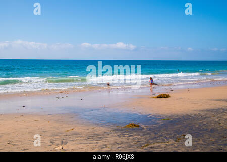 Crystal Cove, California - October 7, 2018: Beautiful flat beach with two children playing in the blue ocean as seen on this date - Stock Photo