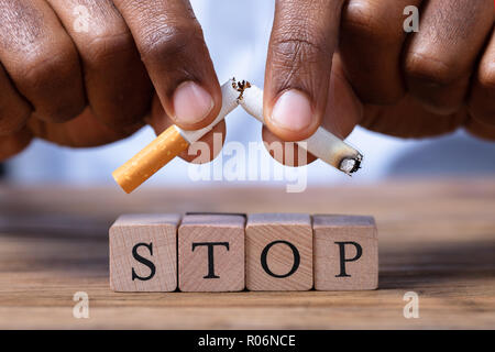Close-up Of A Man's Hand Breaking Cigarette Over Wooden Stop Blocks - Stock Photo