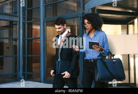 Two business colleagues walking out of office building. Corporate business professionals walking together and talking. - Stock Photo