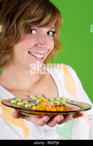 portrait of woman with heap of pills on green background - Stock Photo