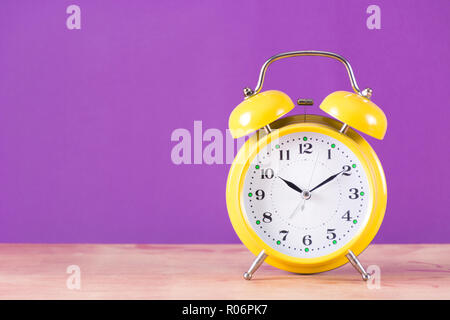 Alarm old retro clock with bell on wooden desk and purple background. Clock is in yellow color. Space for text and design. Time concept image - Stock Photo
