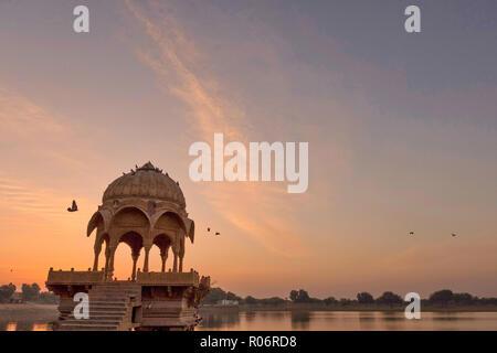 Stunning view of Gadi Sagar temple on Gadisar artificial lake at sunrise in Jaisalmer, India. - Stock Photo