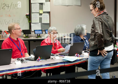 Woman waits to receive ballot while midterm poll worker (election officer) verifies identity of voter during 2018 midterm elections - Virginia USA - Stock Photo