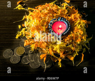 Lit diya and coins placed on black background to celebrate Diwali and Dhanteras - Stock Photo