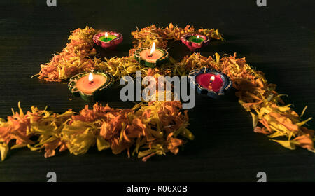 Lit Diyas placed on flower with black background - Stock Photo
