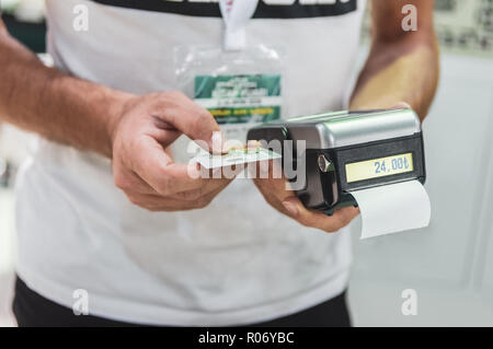 Caucasian seller man holding card machine or POS terminal in his hands. Payment with NFC technology on contactless credit card. - Stock Photo
