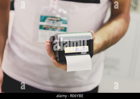 Caucasian seller man holding card machine or POS terminal in his hands - Stock Photo