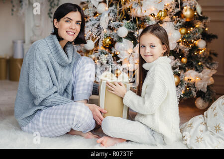 Little child and her mother sit on warm white carpet near decorated New Year tree, holds present in hands, have pleased and happy expressions, glad to - Stock Photo