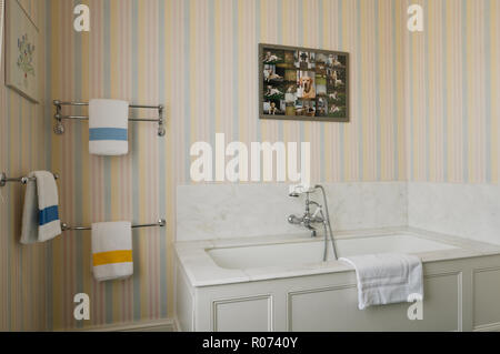 Bathtub with striped wallpaper - Stock Photo