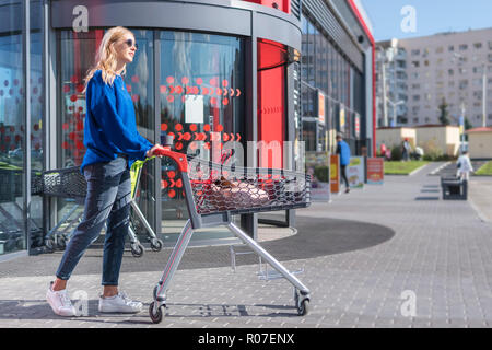 woman with a cart goes to the entrance to the mall - Stock Photo