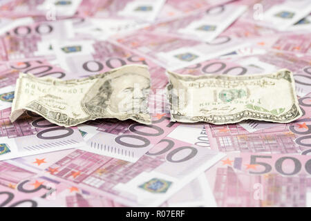 torn one hundred dollars on a background of money with a face value of five hundred euro - Stock Photo