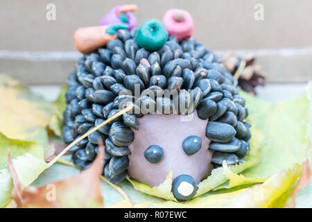 Children crafts - hedgehog from plasticine and seeds instead of needles on autumn leaves - Stock Photo