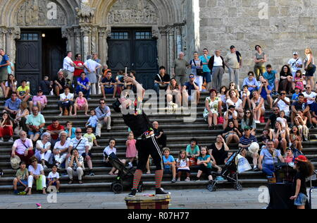 Santiago de Compostela, Spain. August 2018. A fire eater performs in front of the Cathedral. Little girl helper. Platerias Square. - Stock Photo
