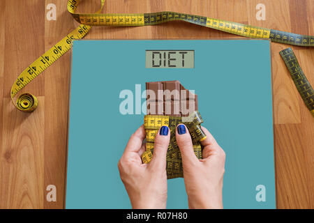 Hands of woman with on weighing scale asking for help to avoid the temptation to eat sweets. Stop eating sweets, healthy diet concept with measurement - Stock Photo