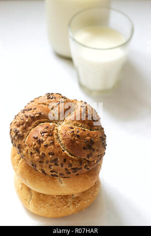 Wheat and rye Kaiser buns with flax and sesame seeds served with milk, healthy breakfast. Selective focus. - Stock Photo
