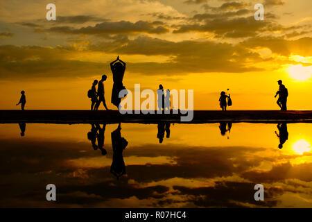 Sunset over the unidentified people on vacation in Tanjung Aru beach, Kota Kinabalu, Malaysia. - Stock Photo