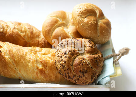 Kaiser wheat and rye flour buns with seeds, mini baguettes with ham and cheese, fresh bread. - Stock Photo