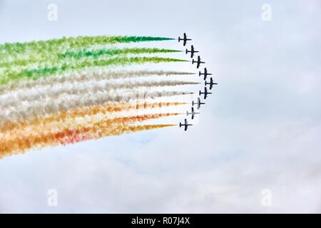 Airforce demonstration wit fighter jets or air planes in v formation with colors of the italian flag against a cloudy sky with copy space - Stock Photo