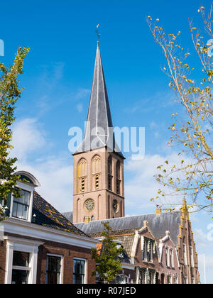 Tower of Saint Werenfridus Church and top facades of traditional houses in historic old town of Workum, Friesland, Netherlands - Stock Photo
