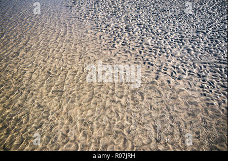Natural textured background of gentle water washing up on rippled sand on an empty beach - Stock Photo
