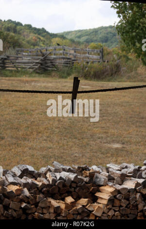Old-style farm life, with clothespin on laundry line and stacked firewood. Frontier Culture Museum, VA - Stock Photo