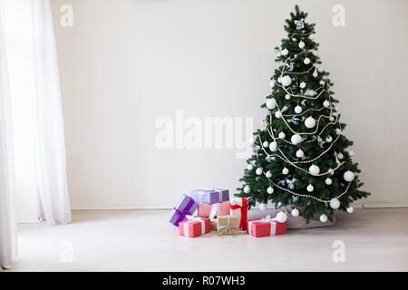 Christmas tree with Christmas gifts in white room - Stock Photo