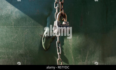 Old metal lock with a chain on green plastic background. - Stock Photo