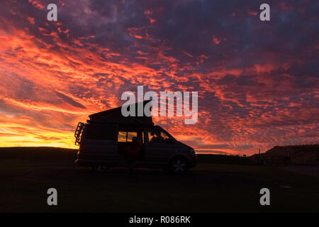 vw camper van silhouetted against brilliant red sunset, Crail, Fife, Scotland, UK - Stock Photo