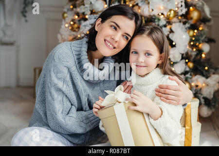 Cheerful brunette female leans at her daugter, embraces her, presents gift box, being in living room near decorated New Year tree. Glad family: mother - Stock Photo