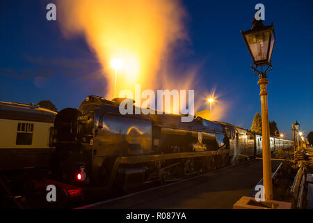 Long exposure, night shot of UK steam locomotive, back-lit, alongside platform, in the dark. Dramatic effect as engine releases steam under pressure. - Stock Photo