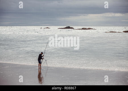 Man fishing from the beach in the Irish Sea on the coast of Anglesey, North Wales, near Rhosneigr, by the Inland Sea, UK - Stock Photo