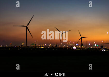 Group of windturbines silhouetted against a twilight sky - Stock Photo
