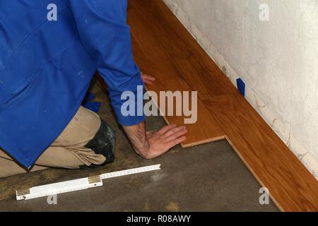 Parquet flooring. Worker laying parquet flooring - Stock Photo
