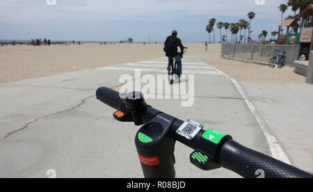 A green Lime-S (Limebike) electric dockless scooter is parked and ready to be rented on the Venice Beach bike path - Stock Photo