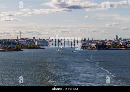 View towards Helsinki city on a summer evening with lots of smaller boats and a car ferry loading, Finland - Stock Photo