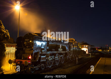 Long exposure, night shot of back-lit, UK steam locomotive, taking on water at SVR station in the dark. Atmospheric as steam released into dark sky. - Stock Photo