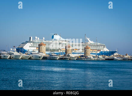 Horizontal photo of big sea ocean cruiser. Boat is in old ancient harbour of Rhodes capital city. Several smaller ships are in front of old stone mill - Stock Photo