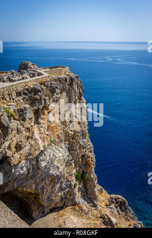 Vertical photo of a part of ancient acropolis above Mediterranean Sea and Lindos town. Acropolis is on Rhodes island. Blue sea and clear sky is visibl - Stock Photo