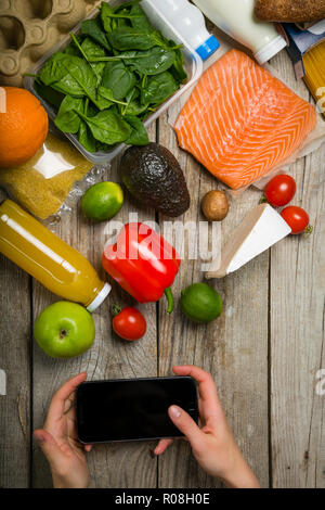 Online shopiing concept - hands holding phone making an order. Grocery shopping concept. Balanced diet concept. Fresh foods with shopping bag on rusti - Stock Photo