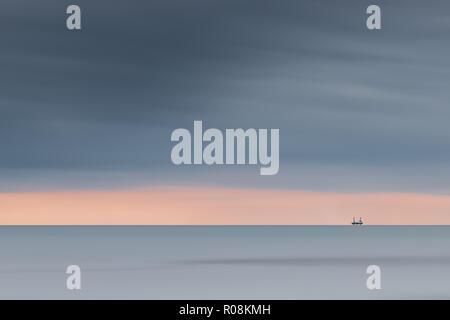 Cleveleys Beach scene near Blackpool with off shore rig on the horizon, Lancashire, England, UK - Stock Photo