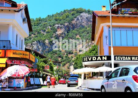 Dalyan, Turkey - July 7th 2018: Street view in Dalyan town, Turkey, with mountain view in the background. - Stock Photo