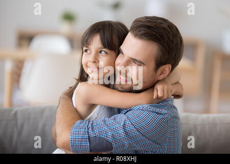 Father and daughter embracing sitting on couch looking at camera - Stock Photo