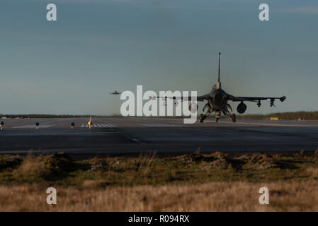 A U.S. Air Force F-16 Fighting Falcon of the 480th Expeditionary Fighter Squadron lines up on the runway at Kallax Air Base, Sweden, as another lifts off for a training mission during Exercise Trident Juncture 18, Nov. 1, 2018. The 480th EFS works closely with their Swedish counterparts at Kallax to ensure safe and effective flight training throughout Trident Juncture 18. (U.S. Air Force photo by 1st Lt. Casey Rodriguez) - Stock Photo
