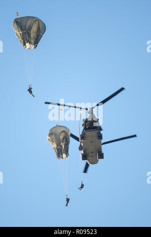 Army paratroopers assigned to the 4th Infantry Brigade Combat Team (Airborne), 25th Infantry Division, U.S. Army Alaska, jump from a CH-47 Chinook helicopter during airborne training at Joint Base Elmendorf-Richardson, Alaska, Nov. 1, 2018. The Soldiers of 4/25 belong to the only American airborne brigade in the Pacific and are trained to execute airborne maneuvers in extreme cold weather and high altitude environments in support of combat, partnership and disaster relief operations. Army aviators from B Company, 1st Battalion, 52nd Aviation Regiment out of Fort Wainwright, operated CH-47 Chin - Stock Photo
