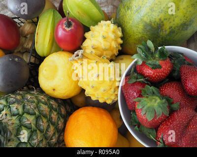 Various colorful tropical fruit, selection in wooden tray over, top view, pineapple, strawberry, dragon fruit, orange, lemon, papaya, star fruit,vegan - Stock Photo