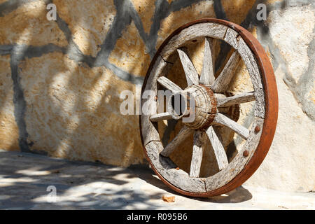 Old wooden cartwheel leaning against the stone wall - Stock Photo